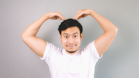 Korean love sign pose. An asian man with white t-shirt and grey background royalty free stock photo