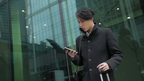 The korean man is standing near the airport and typing the message on his cell phone. The male traveller with stylish haircut is wearing black coat and holding stock video footage