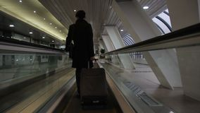 The korean man stands on travelator in the big broght corridor of modern airport. The brunette male wears expensive black suit and holds the handle of his stock video