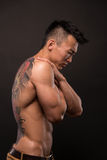 Korean model with tattoo. Male model with a snake and skull tattoo Stock Photography