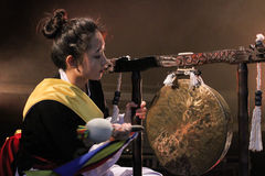 Korean musician.  jing player. A female korean musician wearing traditional outfit and  playing traditional percussion music (samulnori) in jing (large Stock Photography