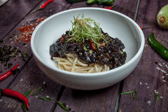 Korean noodle with black sauce in white bowl on wooden table wit Stock Photography