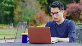 Korean programmer works with a laptop on the street or in a cafe. Asian man wearing glasses works with a laptop. Sitting on the summer terrace in the gardens or stock video