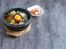 Korean rice mis with vegetables and egg with korean sauce. On wood background Stock Photos