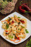Korean salad of cabbage, carrots, sweet peppers - kimchi. Top view, copy space. Pickled cauliflower and carrots and herbs in Korean on a square plate. Wooden royalty free stock photo