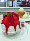 Korean shaved ice topped with strawberry syrup, Bingsu or Bingsoo royalty free stock photography