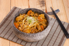 Korean stone bowl of beef noodle with onion on bamboo tray Stock Image