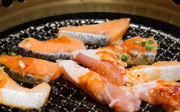 Korean style grilled fish and meat  closeup. Mix of meat and fish Korean style grilled  closeup on hot grid stove Royalty Free Stock Photo