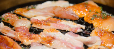 Korean style grilled salmon fish and meat closeup on hot stove Royalty Free Stock Photo