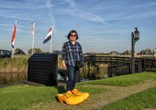 Korean tourist posing in big yellow clogs by the Schermerhorn Museum Mill and visitors center, Stompetoren, Netherlands. Pictured is a female Korean tourist stock photography