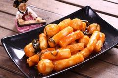 Korean Tteokbokki med chilisås på det svarta uppläggningsfatet Royaltyfri Bild