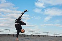 Korean urban style male dancer performing breakdance handstand on top roof