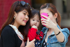 Korean women selfie. MANDALAY,MYANMAR,JANUARY 16, 2015 : Korean women are shooting a selfie (self portrait) with a funny bored little girl in a street of Stock Photography
