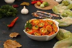 Koreanisch-ähnlicher Salat mit grünen Tomaten und Karotten in einer weißen Salatschüssel auf einem dunklen Hintergrund stockfotografie