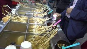 Koreanische Straßen-Nahrungsmittel oden Bestandteile, essen Leute Fischfrikadellen und anderen Imbiss stock footage
