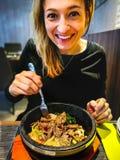 Koreanischer Bibimbap diente in der heißen Stein-dolsot Topfschüssel, die von der kaukasischen lächelnden Frau gegessen wurde, stockfotos