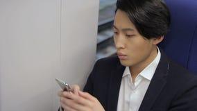 Koreanischer Mann benutzt Telefon beim Sitzen in beweglichem Zug stock footage
