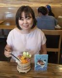 Koreansk kvinna som tycker om matställen i en restaurang i Seattle, Washington royaltyfri foto