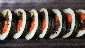 Koreansk maträttgimbap eller kimbap med tonfisk och grönsaker på den mörka keramiska plattan lager videofilmer