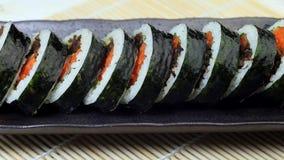 Koreansk maträttgimbap eller kimbap med tonfisk och grönsaker på den mörka keramiska plattan arkivfilmer