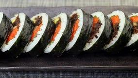 Koreansk maträttgimbap eller kimbap med tonfisk och grönsaker på den mörka keramiska plattan stock video
