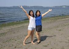 Koreansk moder och Amerasian tonårs- dotter som har gyckel på Alki Beach, Seattle, Washington royaltyfri bild