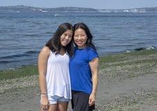 Koreansk moder och Amerasian tonårs- dotter som har gyckel på Alki Beach, Seattle, Washington royaltyfri foto