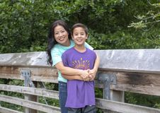 Koreansk moder och hennes Amerasian son som poserar på en träbro i Washington Park Arboretum, Seattle, Washington arkivbilder