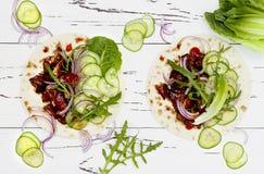Koreanska långsamma lagade mat nötkötttaco med asiatisk gurkavitkålssallad och srirachaketchup Bästa sikt, lekmanna- lägenhet royaltyfri bild