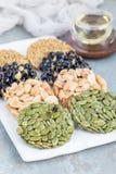 Koreanska traditionella söta mellanmål med jordnötter, pumpafrö, svarta sojabönor och kinesisk bovete på den vita plattan, lodlin Royaltyfri Fotografi
