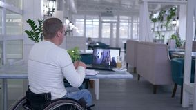 Korespondencyjna edukacja, uczeń obezwładniający mężczyzna w koła krześle pisze notatkach w notatniku i oglądać online szkolenie  zbiory wideo