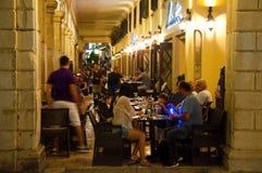 25 Korfu-AUGUSTUS: De toeristen hebben hun maaltijd in een lokaal restaurant op 25 Augustus, 2014 in Kerkyra-stad op het eiland v Stock Afbeelding