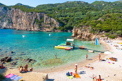 26 Korfu-AUGUSTUS: Het Palaiokastritsastrand, toeristen zonnebaadt op het strand op 26,2014 Augustus op Korfu, Griekenland Stock Fotografie