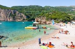 26 Korfu-AUGUSTUS: Het Palaiokastritsastrand, vakantiegangers zonnebaadt op het strand op 26,2014 Augustus op het eiland van Korf Stock Afbeelding