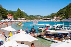 26 Korfu-AUGUSTUS: Palaiokastritsastrand met menigte van mensen die op het strand 26,2014 Augustus op Korfu, Griekenland zonnebad Stock Foto