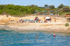 26 Korfu-AUGUSTUS: Sidarystrand, mensen sunbath op de zandige kust op 26,2014 Augustus op het eiland van Korfu, Griekenland Stock Afbeeldingen