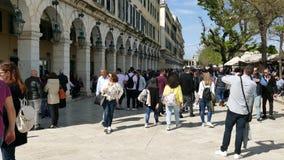 KORFU GREKLAND - APRIL 6, 2018: Gå folk på den Spianada fyrkanten av den Korfu staden, Grekland Huvudsaklig fot- gata Liston Påsk arkivfilmer