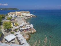 Korfu Grekland - Juni 7, 2017: Den Faliraki stranden Alecos badar den offentliga badningfläcken med En-PLO-restaurangen i den Kor royaltyfria foton