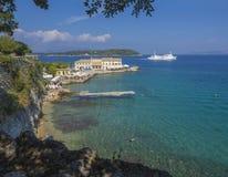 Korfu Grekland - Juni 7, 2017: Den Faliraki stranden Alecos badar den offentliga badningfläcken med En-PLO-restaurangen i den Kor arkivbilder