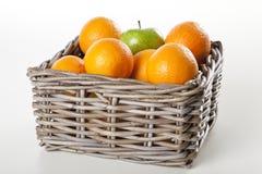 Korg av apelsiner och äpplet Arkivfoton