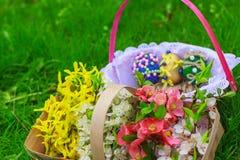 Korg av blommor och en korg med ägg Arkivfoton