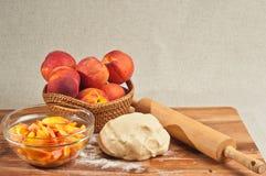 Korg av hela organiska persikor, bunke av skivade persikor Royaltyfri Bild