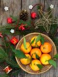 Korg av mogna mandariner, granfilialer och julleksaken på en träbakgrund Selektivt fokusera Arkivfoton