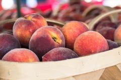 Korg av mogna persikor på bondemarknaden Royaltyfria Bilder