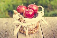 Korg av röda äpplen på en träbakgrund royaltyfri fotografi