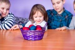 Korg för påskägg och gulliga barn Arkivbilder