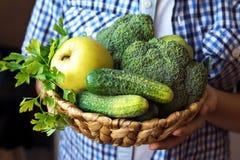 Korg för personhandhåll med gröna grönsaker arkivbild