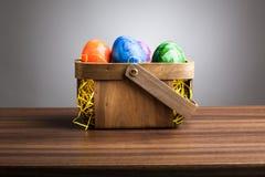 Korg kulöra easter ägg på tabellen, grå bakgrund royaltyfri bild