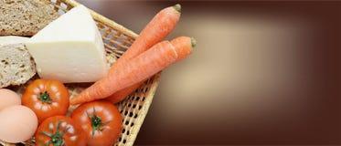 Korg med biologiska frukter, grönsaker, ägg, ost och bröd Arkivbilder