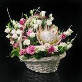 Korg med blommor på svart Arkivfoto
